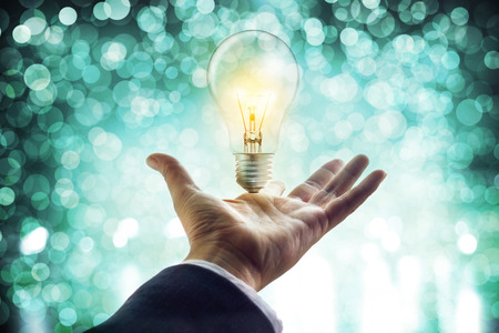 human energy: Hands of a businessman reaching to towards light bulb, business inspiration concept