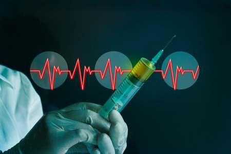inyeccion intramuscular: jeringa en el guante de la mano de una Frecuencia Card�aca en laboratorio azul antecedentes m�dicos