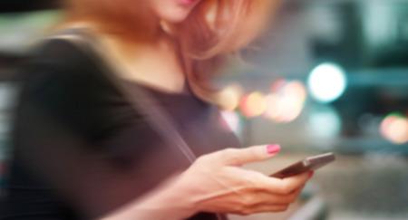 kleurrijke vrouw gebruikend op de mobiele telefoon, zacht en vervaging-concept Stockfoto