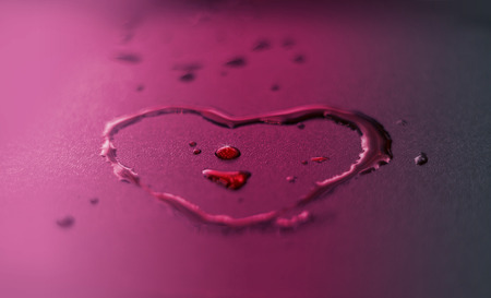 clean heart: vibrant water drops heart shape on purple background Stock Photo
