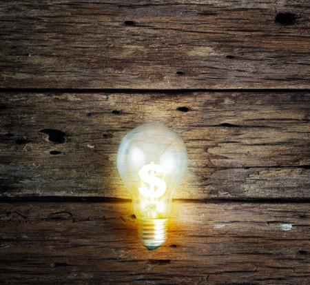 signo pesos: Bombilla y signo de dólar en la pared de madera, concepto de negocio