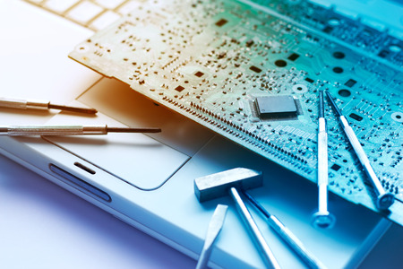 colorful electronic board and tools repairs on old laptop, toned vibrant concept Stockfoto