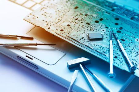 kleurrijke elektronisch bord en gereedschappen reparaties aan oude laptop, afgezwakt levendige begrip Stockfoto