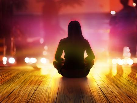 Frauen sind in der Nacht und Lichtstrahlen zu meditieren in der Stadt Standard-Bild
