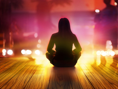 meditation woman: women are meditating at night and rays of light  in the city
