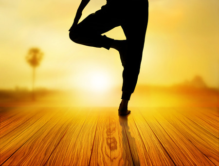 yoga sunset: woman yoga exercise in sunrise, soft and blur concept Stock Photo