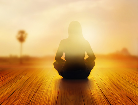 silencio: mujer estaba meditando en la salida del sol y los rayos de luz sobre el paisaje, el concepto blando y desenfoque