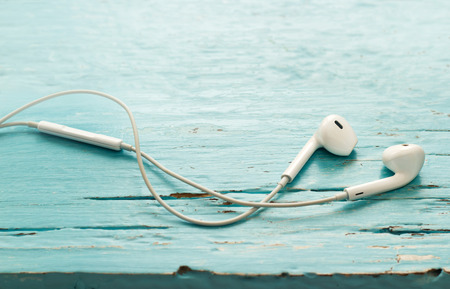ear phones: vintage pastel color tone style of earphones on green vibrant color wooden background