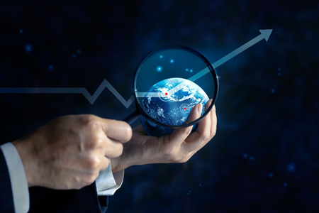business focus: business man looking a business graph upwards on globe and stars by useing magnifying glass in hands, business concept, soft focus and blur Stock Photo