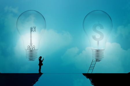 dollar signs: business woman stand on a cliff  with key and dollar signs in light bulbs on a blue background, business concept Stock Photo