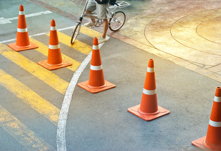 abstract colorful traffic cones and bicycle man on the street, pastel and blur concept