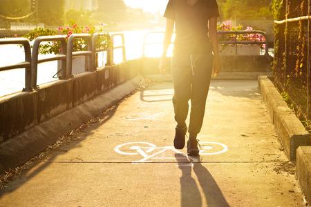 bike lane: sport woman walk on symbol bike lane in vibrant sunrise, soft focus