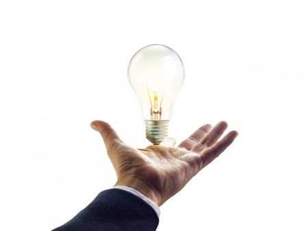 powerful creativity: Hands of a businessman reaching to towards light bulb, business inspiration concept