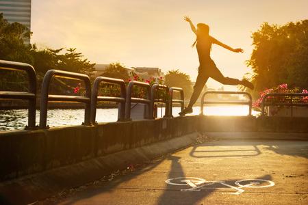 bike lane: sport women jumping on the bike lane in the sunrise, soft focus and blur