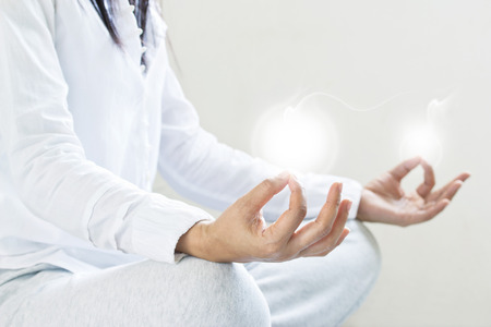 meditation room: woman meditating of purity energy insight on gray background, selective focus