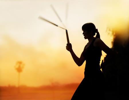 nunchaku: martial arts, women and nunchaku in hands silhouette in sunset