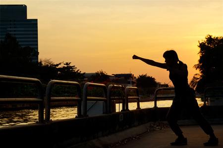 arte marcial: las mujeres de boxeo ejercicio y artes marciales silueta en la puesta del sol Foto de archivo