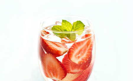 warm color: glass delicious refreshing drink of strawberry and apple with mint on blue background, infusioned water, soft focus and warm color tone Stock Photo