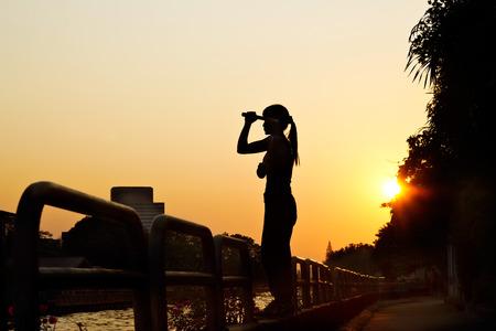 nunchaku: women and nunchaku in hands silhouette in sunset, martial arts