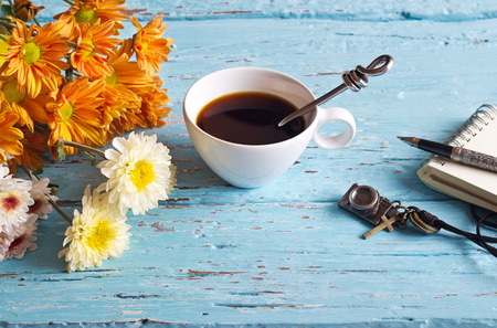 drinks on bar: coffee cup and vibrant flower, paper note of vintage pastel color tone style on blue wooden, soft focus Stock Photo