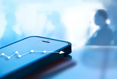 blue tone: Abstract mobile phone and graph chart growth on screen and business man background, soft focus and blur, blue tone style Stock Photo