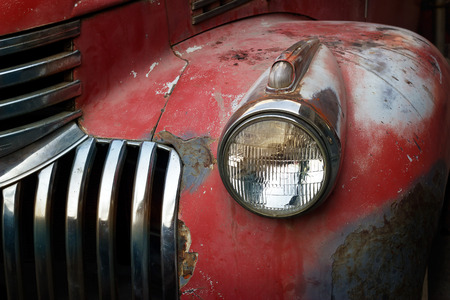eyesore: Vintage rusty red truck car with a new headlight, soft focus