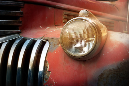 eyesore: Vintage rusty red truck car with a new headlight in the sunshine, soft focus Stock Photo