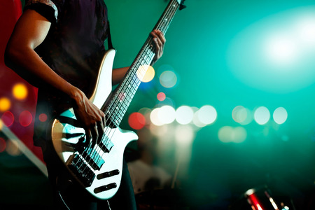 stage performer: Guitarist bass on stage for background, colorful, soft focus and blur concept Stock Photo