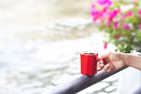 glass fence: coffee red cup on a fence of canal nature background