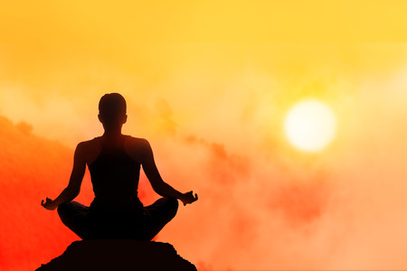 women meditating on high moutain in sunset background
