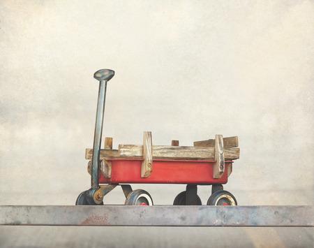 juguetes antiguos: Juguetes rojos de tracción de la carretilla, carro viejo oxidado, el tono del color de la vendimia en el papel de grano
