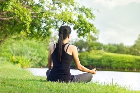 Sport girl meditating in nature green park at the sunrise 스톡 콘텐츠