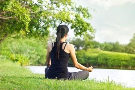 mujer meditando: Muchacha del deporte meditando en la naturaleza verde parque en la salida del sol