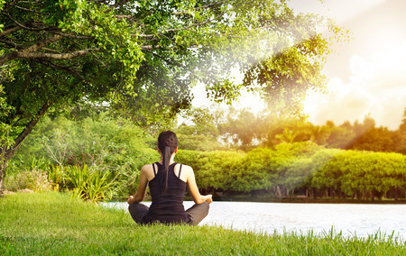 Sport girl meditating in nature green park at the sunrise Archivio Fotografico