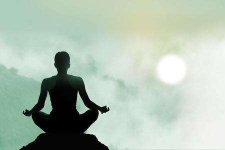 山の夕日を背景にカラフルな瞑想の女性