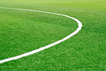soft   focus: Green soccer field grass with white mark line, soft focus