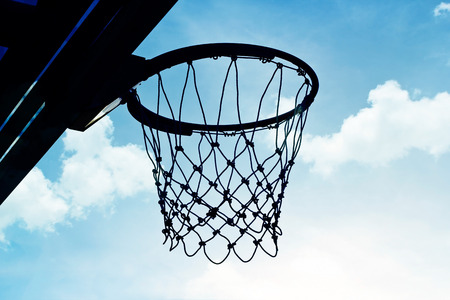 intramural: Silhouette basketball hoop outdoors in the cloud and blue sky