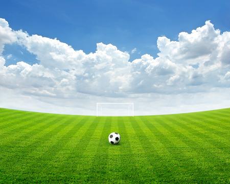 terrain de foot: Ballon de football sur le terrain vert, ciel bleu avec des nuages ??en été, soft focus Banque d'images