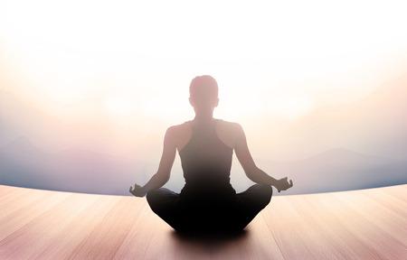 silencio: mujer estaba meditando en la mañana y rayos de luz sobre el paisaje, vibrante concepto suave y desenfoque Foto de archivo