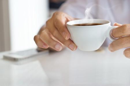 hombre tomando cafe: hombre de negocios y una taza de café en la mano, texto en blanco y enfoque suave
