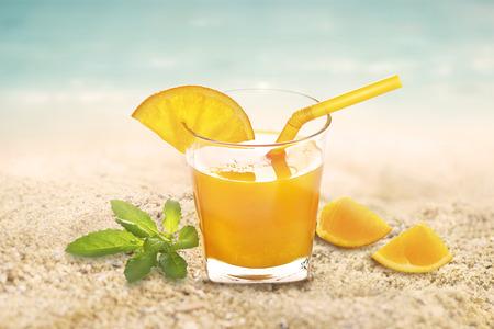 vaso de jugo: Zumo de naranja con la menta en vidrio en el mar de arena de playa el día de verano Foto de archivo