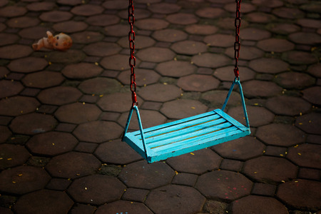 empty of people: Single blue swing empty people and doll at dark night Stock Photo