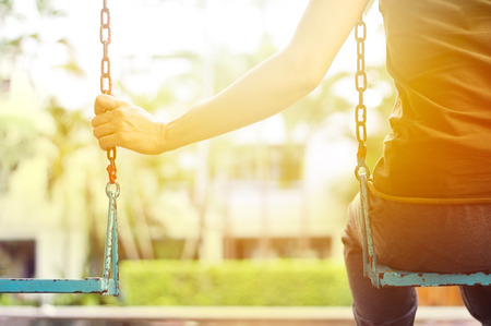 columpios: Mujer sola falta a su novio mientras se mece en la villa del parque en la mañana Foto de archivo