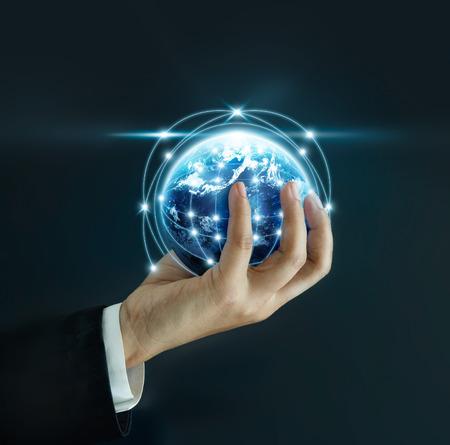 L'homme d'affaires tenant le petit monde dans ses mains sur fond sombre, éléments de cette image fournie par la NASA