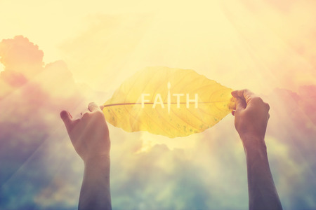 faith hope love: abstract, holding a yellow leaf in the colorful sky of faith, vintage color tone and soft focus