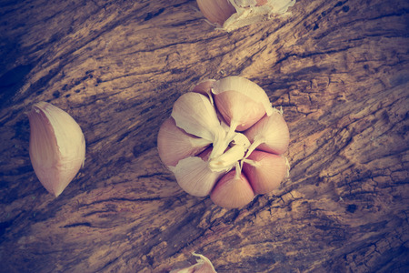 wooden color: Garlic on the wooden spoon and wooden background, Vintage color, top view Stock Photo