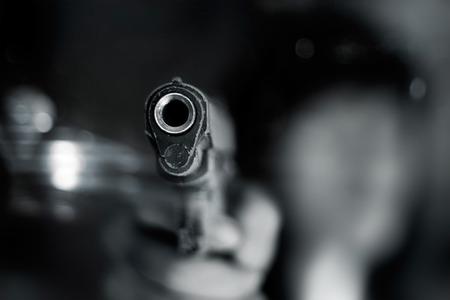 pistolas: Blanco y negro, mujer apuntando una pistola antigua a frente con una mano sobre fondo oscuro
