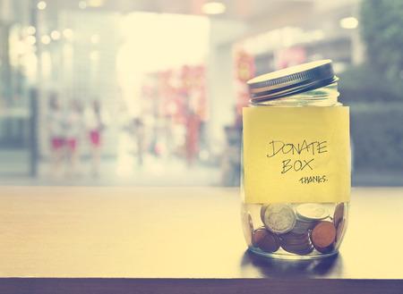 募金箱、ガラス瓶、ヴィンテージ色のトーンでコイン