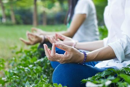 vrouwen mediteren buiten in het groen park op de natuur achtergrond