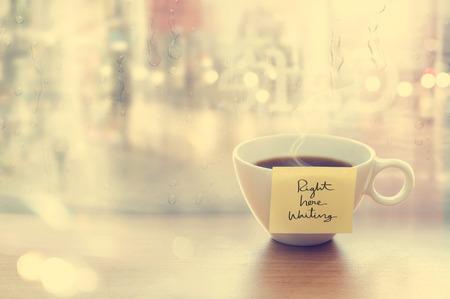 lluvia: Humeante taza de café con la taza mensaje de la emoción en la tienda de café, delante del espejo y la ventana de gota de agua, color de la vendimia y el concepto blando